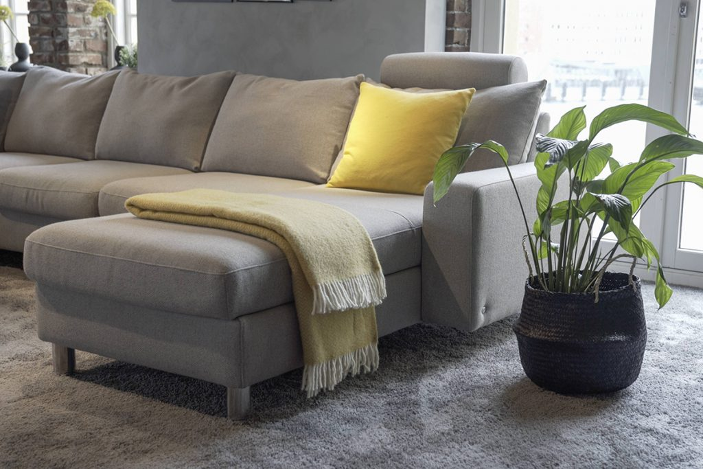 Das Stressless Sofa-Modell E200 zeigt sich im Ausstellungsraum Ekornes Bua in einem hellen Grau.