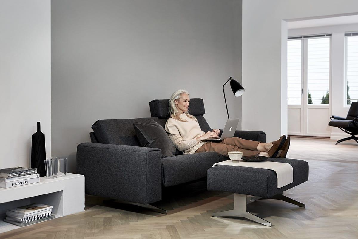Das Stressless Bella Sofa in Kombination mit dem passenden Hocker und Tischplatte sorgt für eine entspannende und stilvolle Atmosphäre im Wohnraum.